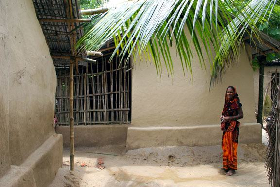 Bangladesh couple sitting in front of home
