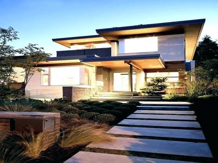 The very modern exterior of the home features red brick and dark brown wood  siding that make the boxy design feel welcoming