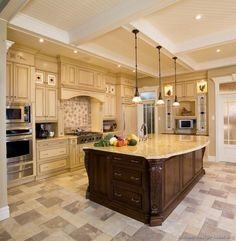 Luxury white kitchen with marble island,  hanging pots and pans and hardwood flooring
