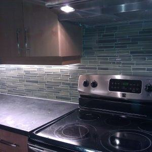 Back painted glass panels add a pop of teal to this loft kitchen in New  Jersey