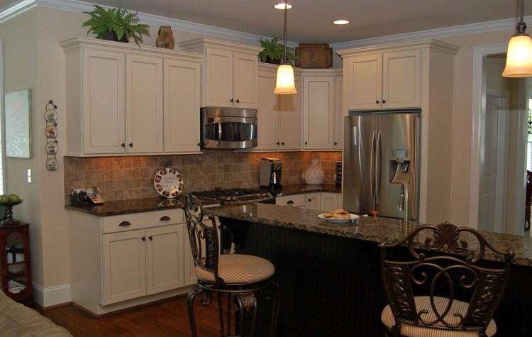 Off white with large range hood, black granite countertop, brick pattern  backsplash, 48